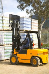 Fork lift operator near pile of pallets