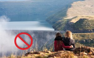 Two girls on hill sitting across hydrodam