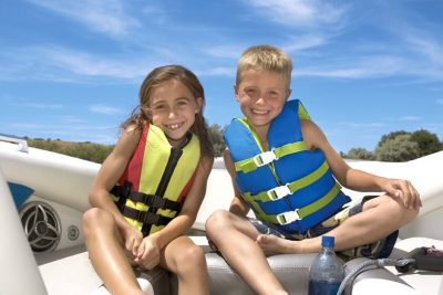 Young girl and boy smiling on boat wearing life jackets