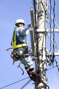 Lineman attached to pole working on equipment